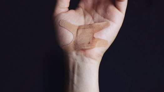 Wounded hand with a band-aid
