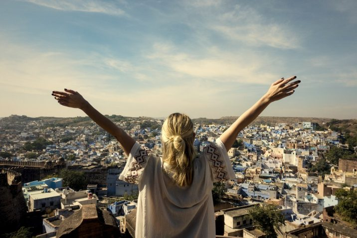 Woman feeling alive with arms outstretched on a mountain