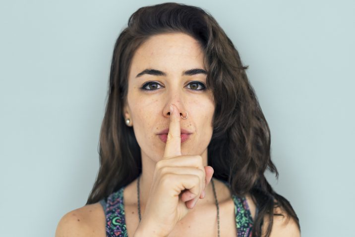Silence - Woman holding finger in front of her mouth