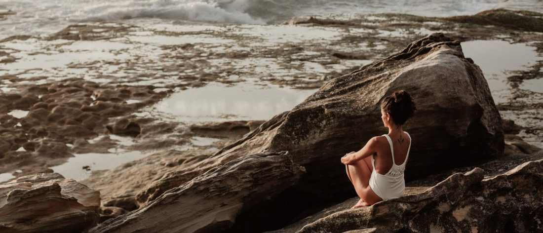 Woman sitting on rocks looking at the ocean