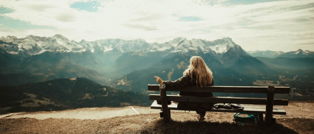 Woman on bench looking at mountains - Being and Enlightenment