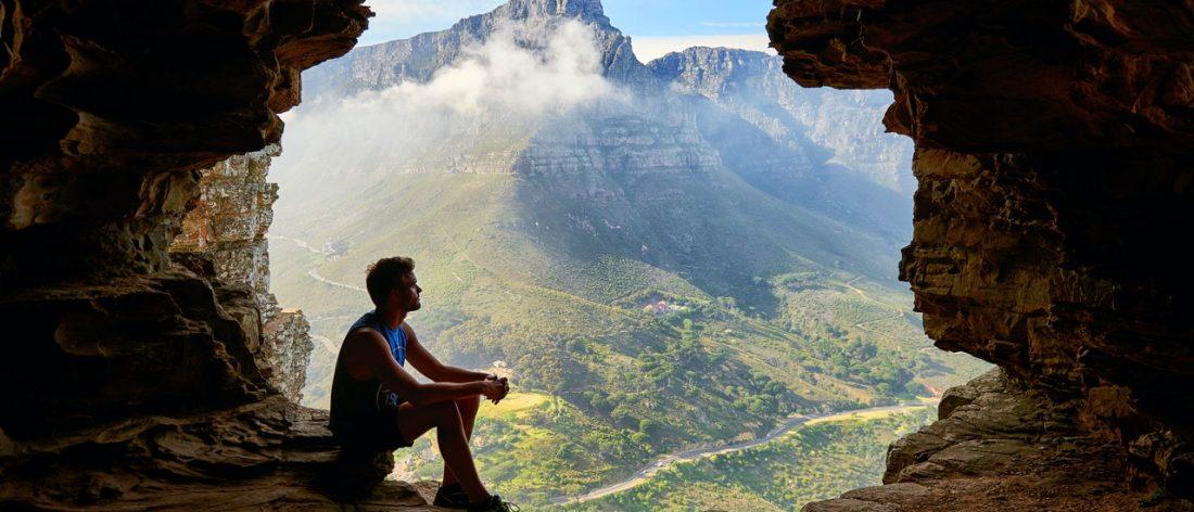 Man in cave contemplating awareness