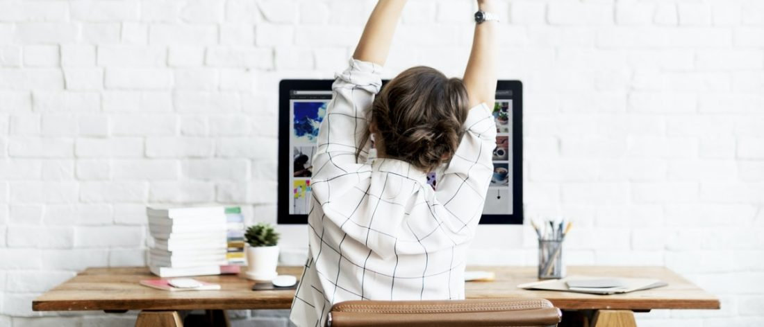 Woman stretching at her computer