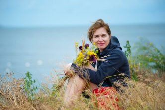 Middle aged woman holding flowers be ocean