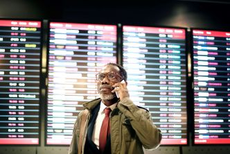 Man in front of plane schedule experiencing modern stress
