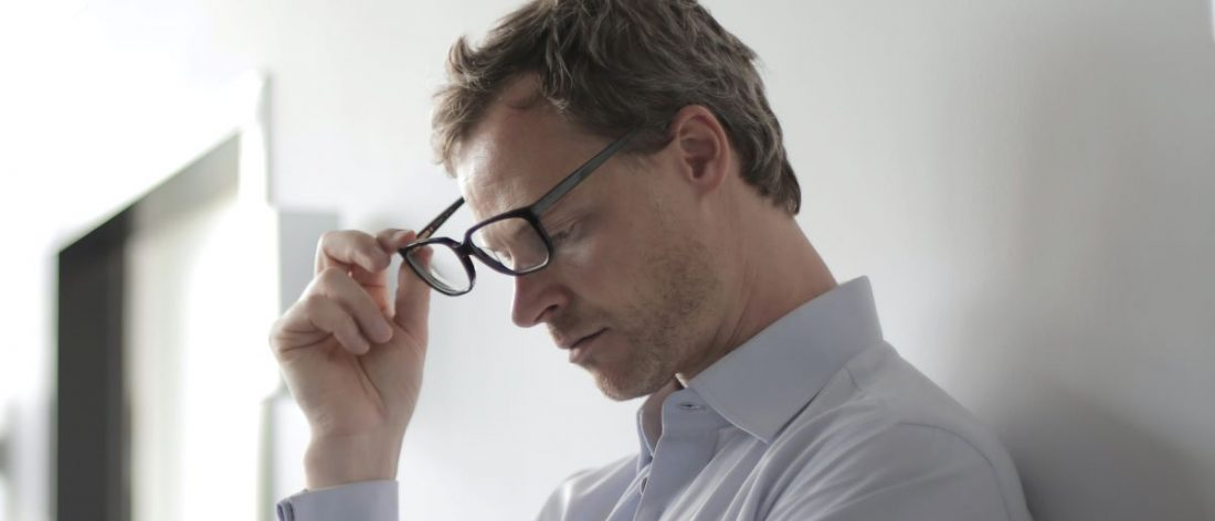Man removing glasses