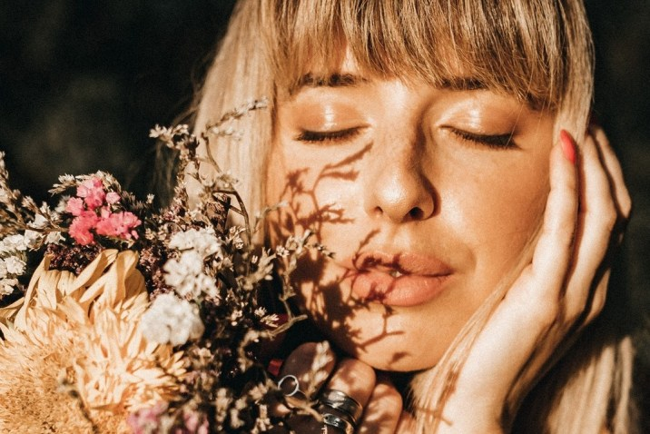 Vibrant healthy woman smelling flowers