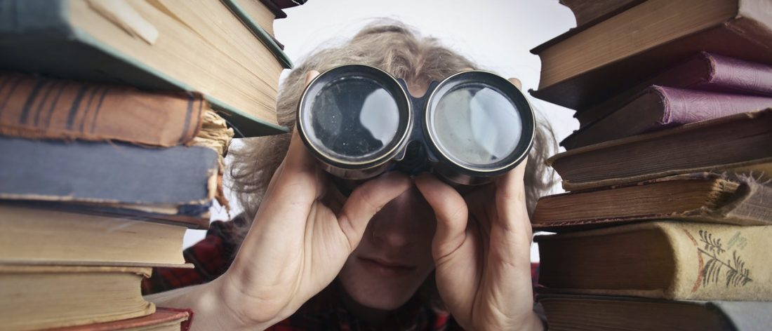 Person looking through books and binoculars