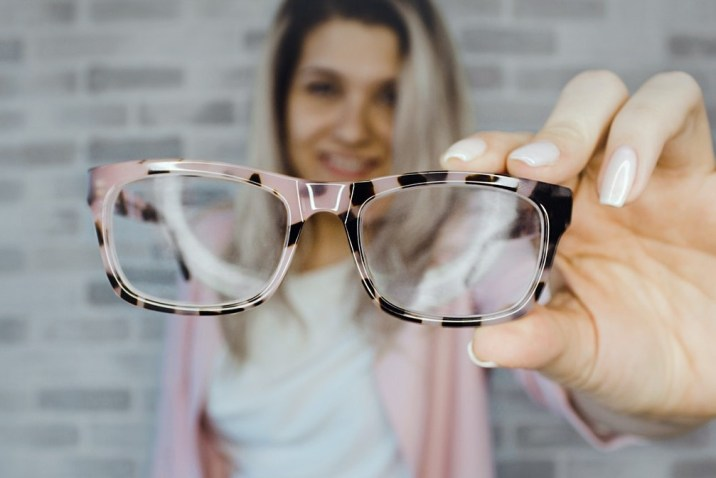 Woman holding eyeglasses - what they say about you