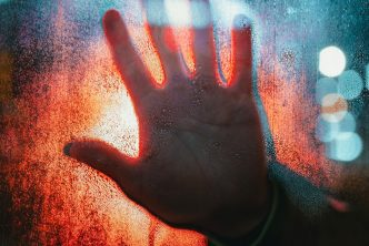 Dark hand on glass with lights in background - Face fear