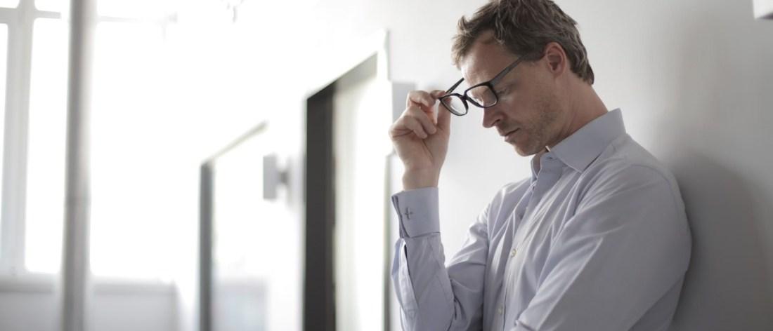 Stressed man taking off glasses