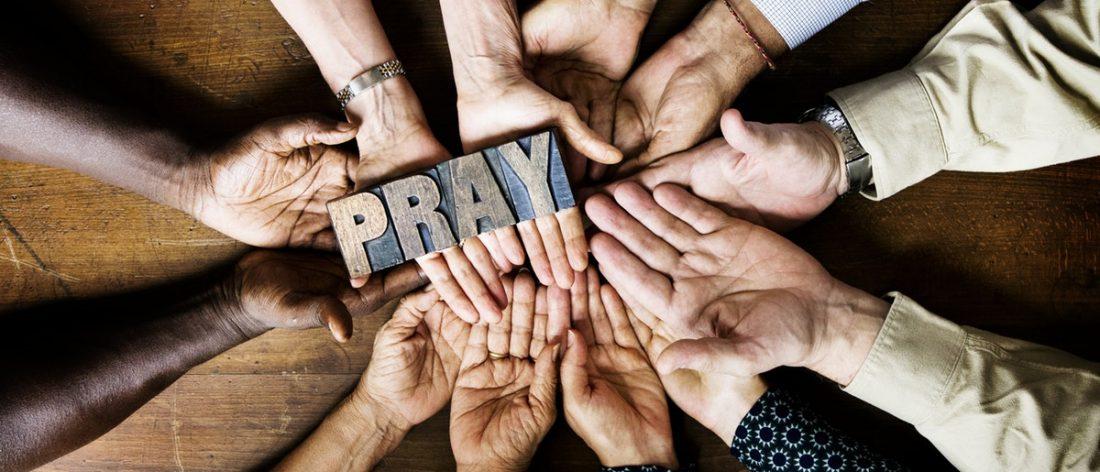 Many hands grabbing a woodblock that spells Pray