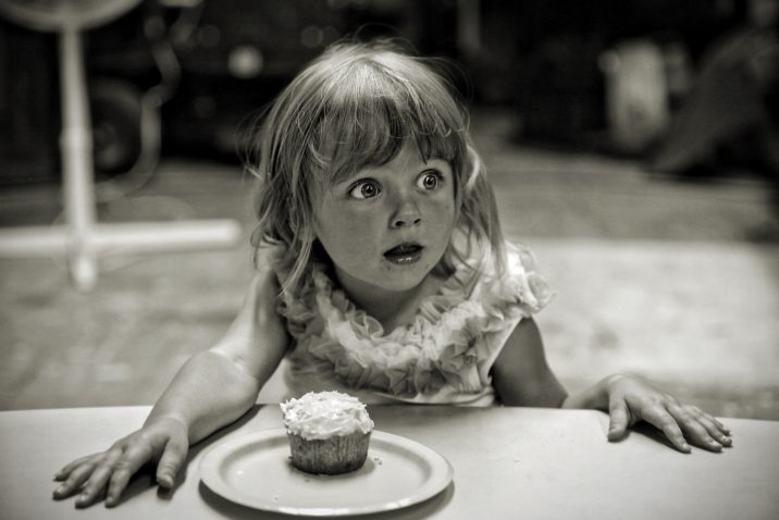 Girl about to eat a cupcake