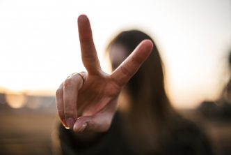 A woman making the peace sign