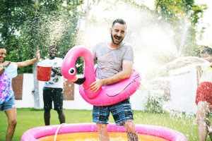 Man in a kid pool getting sprayed with water by his family and friends