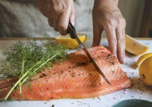 A man slicing raw salmon