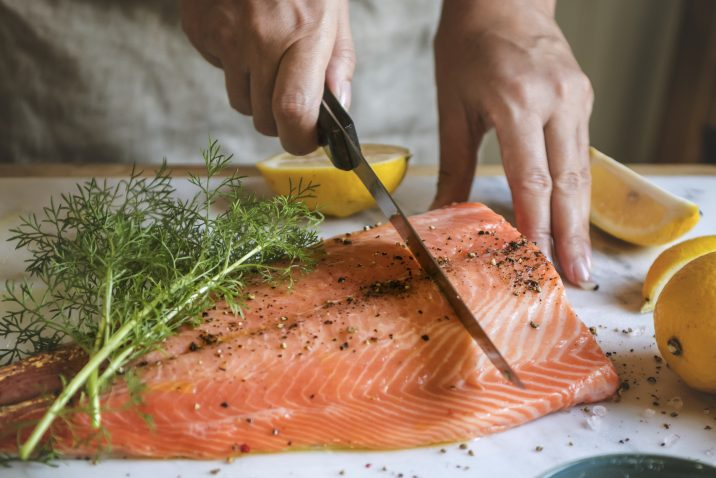 A man slicing raw salmon