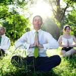 A group of of 4 people meditating in the forest in their business clothes