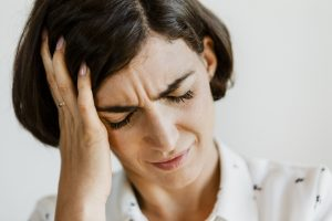 A woman holding her hand to her head in pain