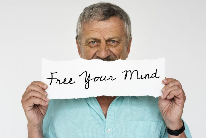 Man holding a sign saying Free Your Mind