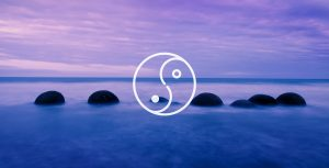 Ying Yang overlaid on top of rocks in the ocean