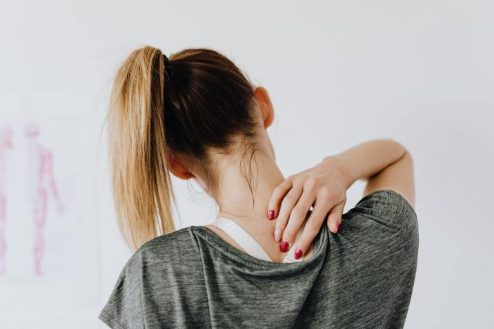 Woman rubbing her back - Listening to Your Symptoms