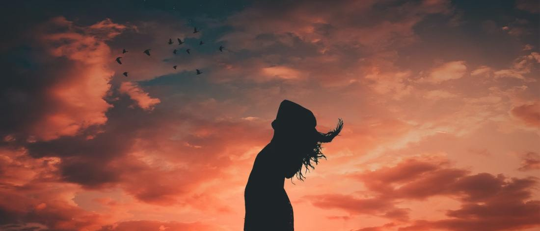 Woman looking at sunset - Stillness and a free mind