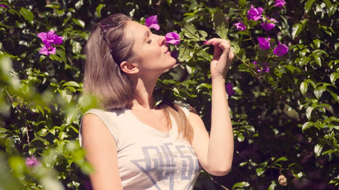 Woman with flowers using her fives senses